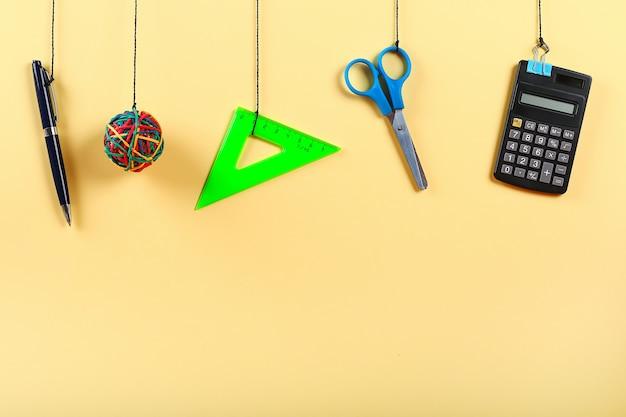 Schoolbenodigdheden hangen aan touw. schoolbenodigdheden op geel. terug naar school-concept Premium Foto