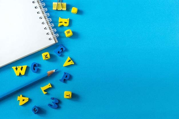 Schoolbenodigdheden op een blauwe achtergrond. school en leraar dag concept. houten letters op de tafel met kopie ruimte. Premium Foto