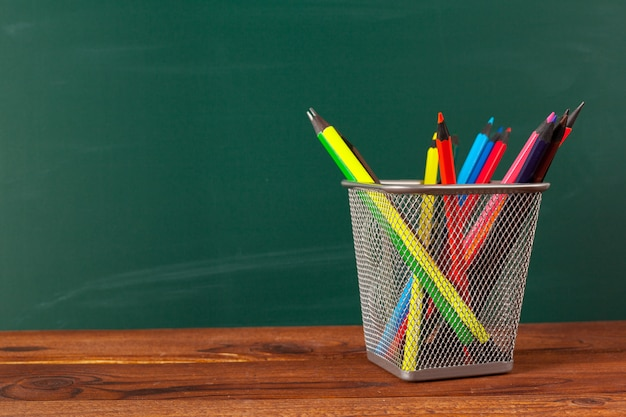 Schoolbenodigdheden op een houten tafel en schoolbord achtergrond Premium Foto