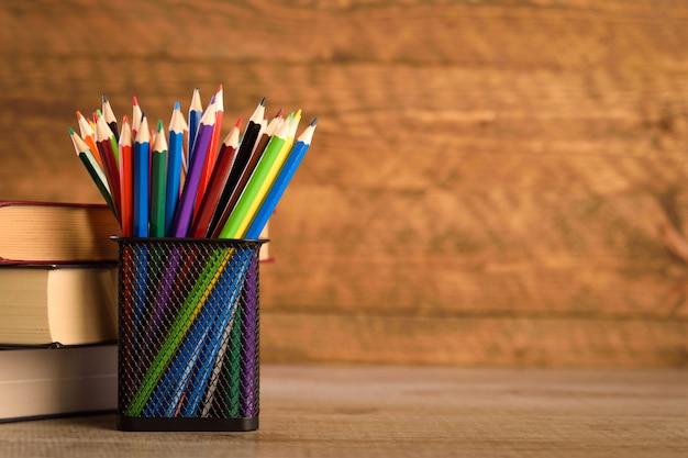 Schoolbenodigdheden op een warme, mooie houten achtergrond. gekleurde kinderpotloden in een kast met zwarte houder voor briefpapier. Premium Foto