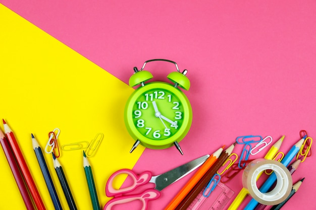 Schoolbenodigdheden op roze en geel papier Premium Foto