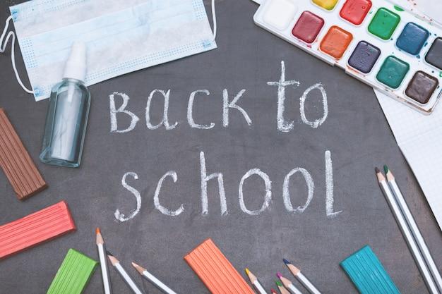 Schoolbenodigdheden op zwarte bord Premium Foto