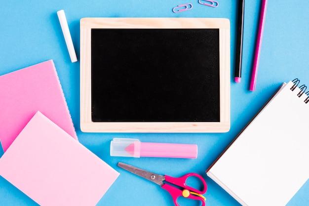 Schoolbord en schoolhulpmiddelen op gekleurde oppervlakte Gratis Foto