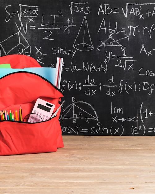 Schoolbord met wiskundige formules en rode schooltas voor meisje Gratis Foto