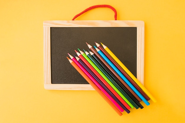 schoolbord onder kleurpotloden  gratis foto