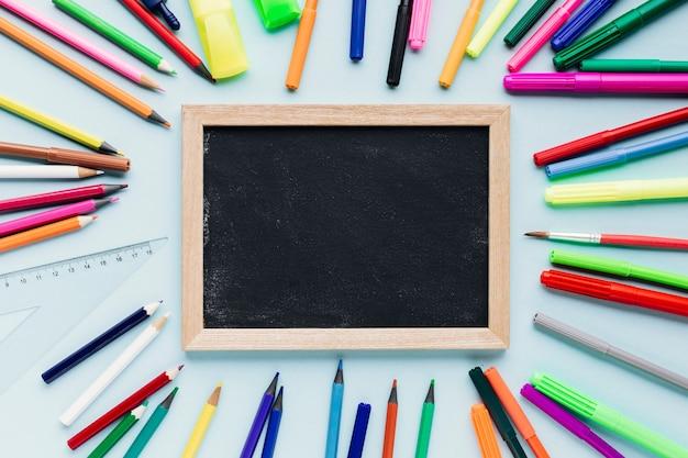 Schoolbordlei naast heldere potloden Gratis Foto