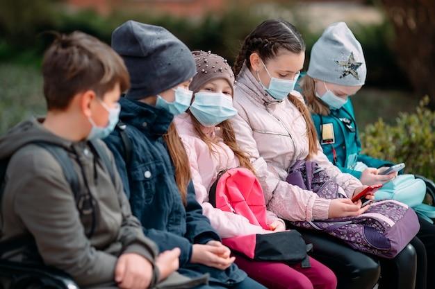 Schoolgaande kinderen in medische maskers zitten op een bankje. Premium Foto