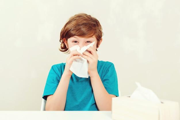 Schooljongen die loopneus blaast. zieke jongenszitting bij bureau. kid met behulp van papieren servetten. allergisch kind, griepseizoen. Premium Foto
