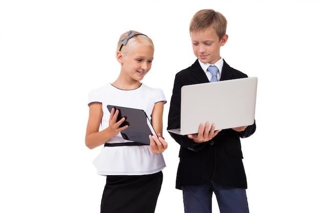 Schooljongen en schoolmeisje met laptop met een tablet op wit Premium Foto