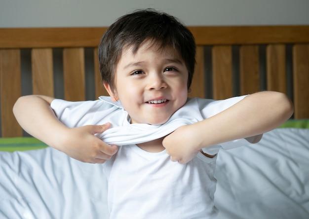 Schooljongen in bed zitten en proberen om zijn doek met lachend gezicht te dragen, schattige jongen jongen aankleden en maak je klaar voor school, kind dressing uniform in bed kamer klaar naar school, terug naar school-concept Premium Foto