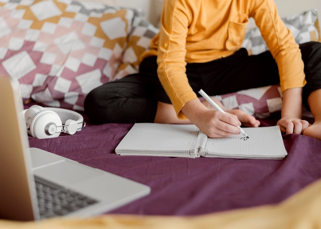 Schooljongen in bed zitten en schrijft Gratis Foto
