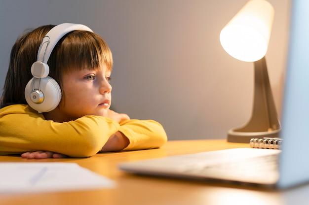 Schooljongen in geel overhemd met virtuele lessen Gratis Foto