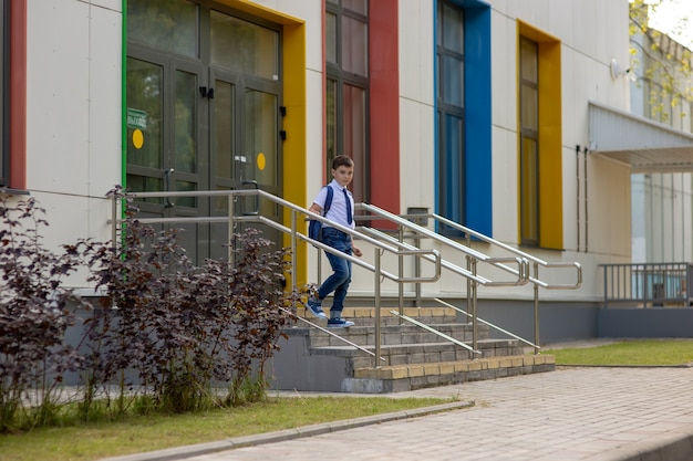 Schooljongen in wit overhemd, blauwe das en rugzak loopt de trap af van de school Premium Foto