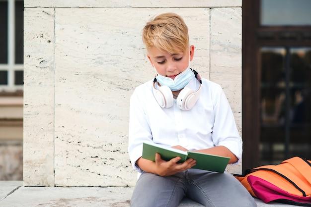 Schooljongen met gezichtsmasker ter bescherming tegen coronavirus. terug naar school-concept. onderwijs tijdens pandemie. moe jongen in veiligheidsmasker na lessen. coronavirus en schoolleven. Premium Foto