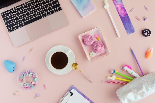 Schoolkantoorbehoeften met kop thee met heemst en eenhoornpen, lamapotlood en laptop op roze. Premium Foto