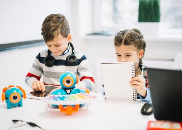 Schoolkinderen bezig met het schrijven van notities en het gebruik van digitale tablet in de klas Gratis Foto