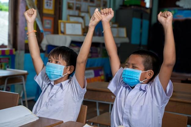 Schoolkinderen die een beschermend masker dragen om te beschermen tegen covid-19 leren in de klas, onderwijs, basisschool. Premium Foto