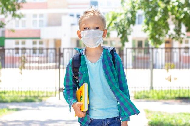Schoolkinderen in een beschermend masker met een rugzak en een leerboek in hun handen. in een t-shirt en een geruit overhemd Premium Foto