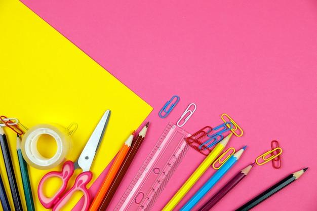 Schoollevering op roze kleurenachtergrond. terug naar school concept flatlay. items voor de school. Premium Foto