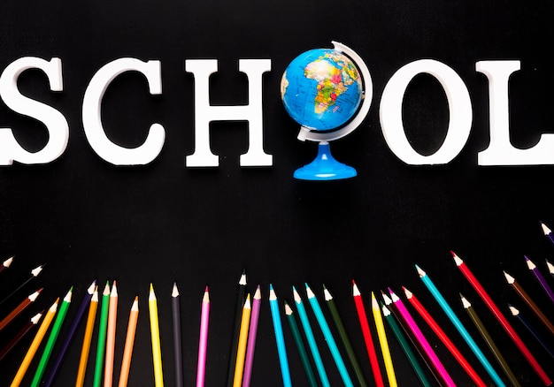 Schoollogo en kleurrijke potloden Gratis Foto