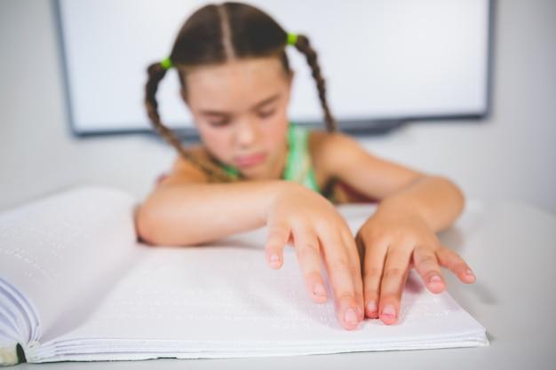 Schoolmeisje dat een braille-boek in klaslokaal leest Premium Foto