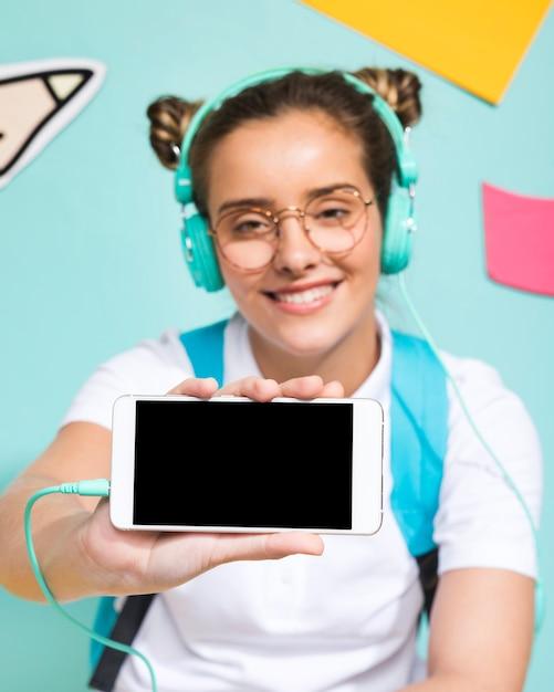 Schoolmeisje die een smartphonesjabloon voorstellen Gratis Foto