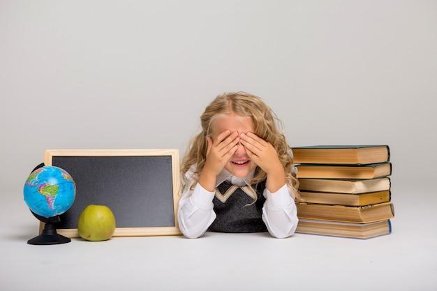 Schoolmeisje met boeken en leeg tekenbord op witte achtergrond Premium Foto