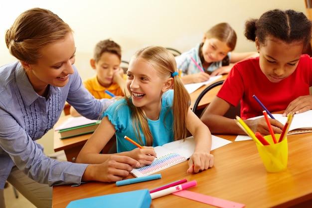 Schoolmeisje met een goede tijd met de leraar Gratis Foto