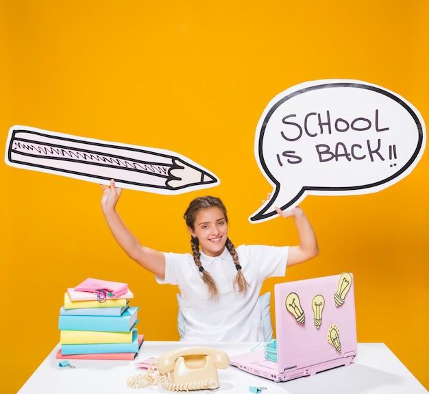 Schoolmeisje op bureau met laptop in de stijl van memphis Gratis Foto