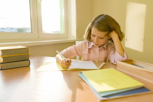 Schoolmeisje, zittend aan tafel met boeken en schrijven in notitieblok Premium Foto