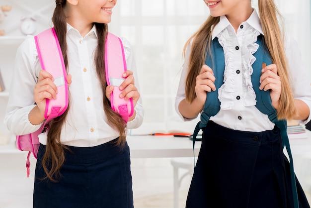 Schoolmeisjes die zich met rugzakken bevinden Gratis Foto