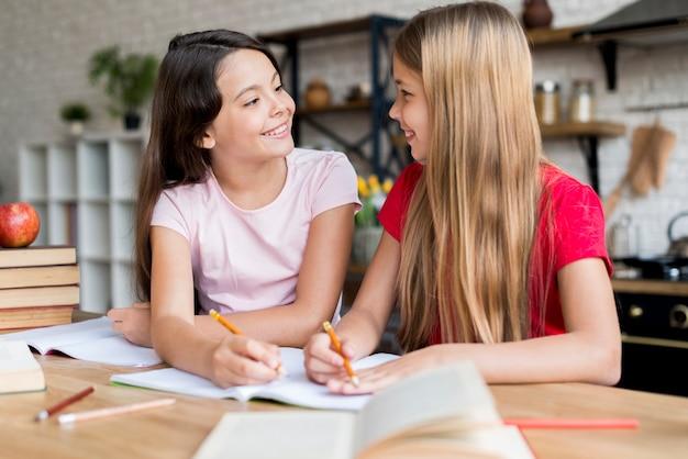 Schoolmeisjes huiswerk maken en naar elkaar kijken Gratis Foto