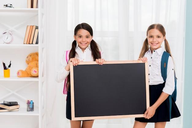 Schoolmeisjes in uniform met schoolbord Gratis Foto