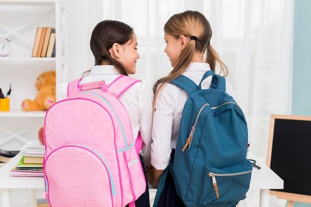 Schoolmeisjes met rugzakken kijken naar elkaar Gratis Foto