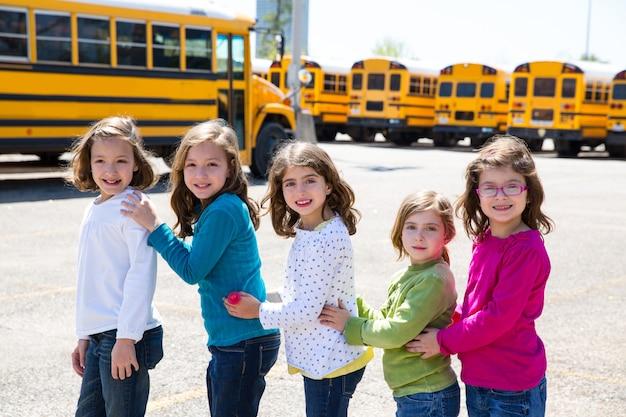 Schoolmeisjes vrienden op een rij lopen van schoolbus Premium Foto