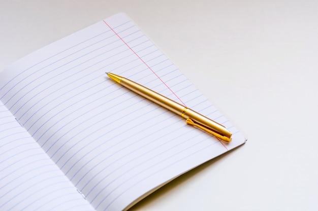 Schoolnotitieboekje en gouden ballpoint op een lichte achtergrond. Premium Foto