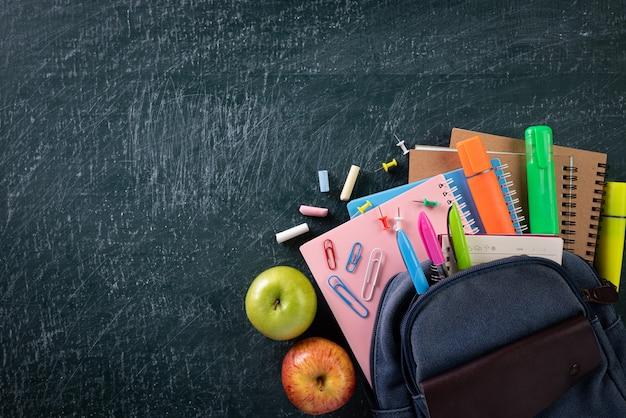 Schoolrugzak en schoolbenodigdheden met schoolbordachtergrond Premium Foto