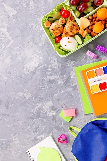 Schoolspullen en lunchbox met eten voor kinderen. kleurrijke kantoorbehoeftenlay-out op veelkleurige achtergrond, exemplaarruimte Premium Foto