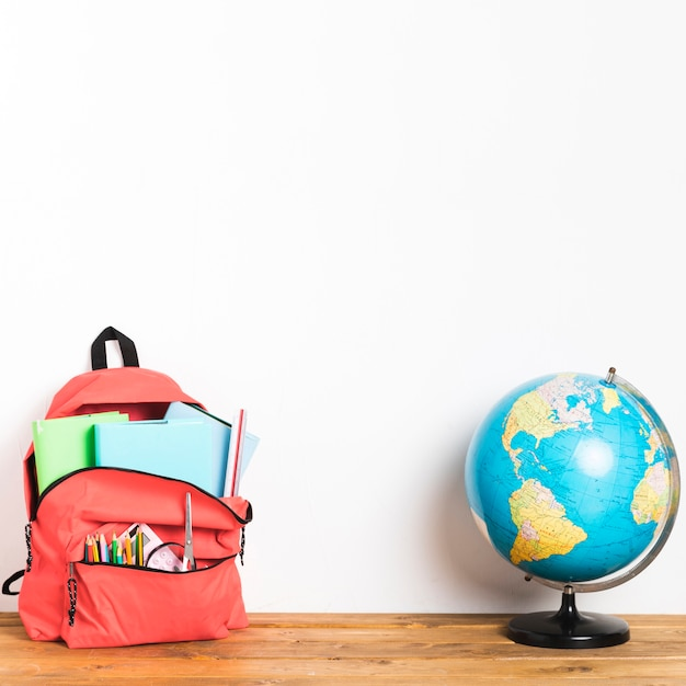 Schooltas met globe op tafel Gratis Foto