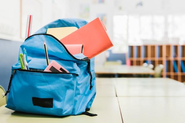 Schooltas met verschillende hulpmiddelen op bureau Gratis Foto