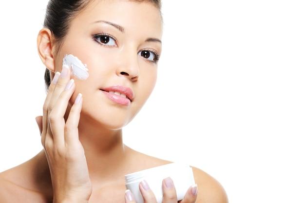 Schoonheid aziatische vrouwelijke huidverzorging van haar gezicht door cosmetische crème op haar wang toe te passen Gratis Foto