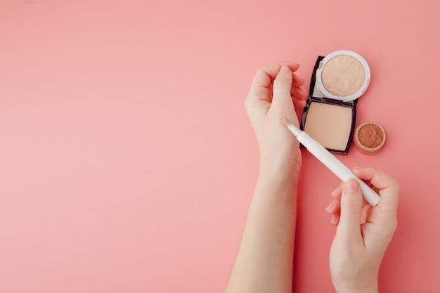 Schoonheid blogger vrouw handen met fles en buis spa professionele hi-end cosmetica op roze achtergrond, minimalisme concept, warme gezellige tonen en copyspace Premium Foto