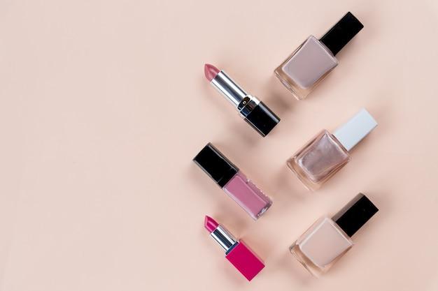 Schoonheid concept. set van professionele make-up cosmetica op pastel achtergrond. cosmetica set. decoratieve cosmetica-objecten, nagelflessen, lippenstift. kopie ruimte Premium Foto