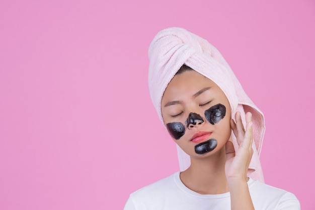Schoonheid cosmetische peeling. jonge vrouw met zwarte peeling masker op huid cosmetische huidverzorging peeling product op het gezicht op een roze. Gratis Foto