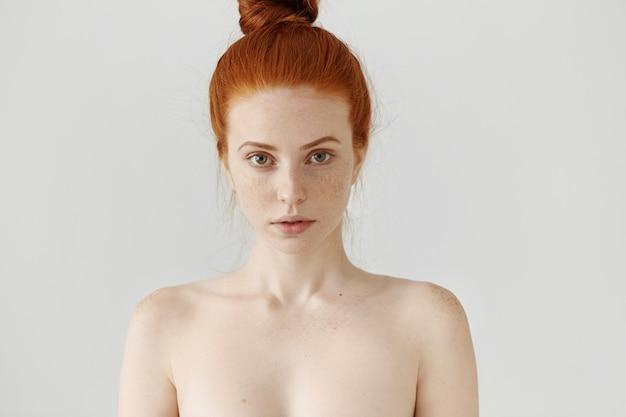 Schoonheid en huidverzorging concept. prachtige jonge gember europese vrouw met tedere trekken die met een subtiele glimlach kijken, topless poseren Gratis Foto