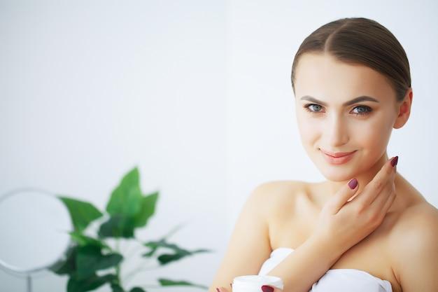 Schoonheid en verzorging. gelukkig lachende jonge vrouw houdt crème voor gezicht. meisje na douche. morning face care. pure huid. Premium Foto