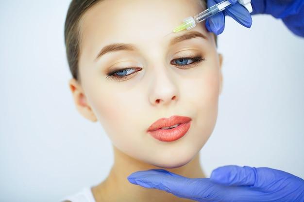 Schoonheid en verzorging. portret van een jonge vrouw met een mooi gezicht. een schoonheidsspecialist maakt injecties. hoge resolutie Premium Foto