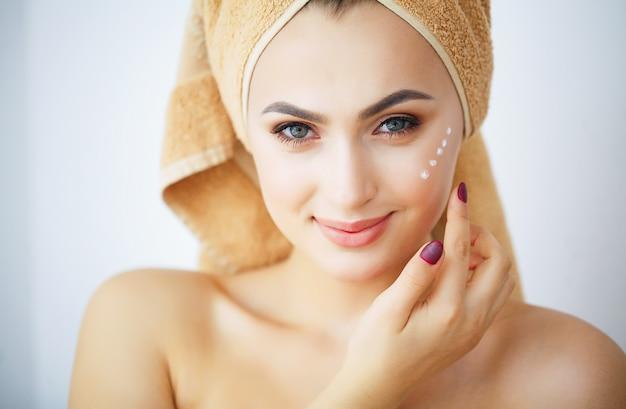 Schoonheid en verzorging, portret van een meisje met een bruine handdoek op het hoofd, Premium Foto