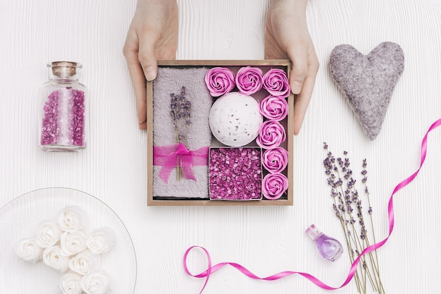 Schoonheid geschenkdoos. spa relax home met lavendelbloemen en lavendelolie, badbom, zeezout, badrozen, grijze handdoek Premium Foto