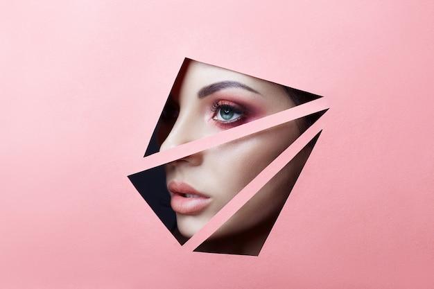 Schoonheid gezicht rode make-up ogen jong meisje in spleet gat van rozerood papier. Premium Foto